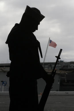 A member of the honor guard stands in silence as names