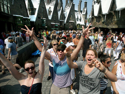 Three weeks after the attraction's grand opening, Potter fans (from left) Jackie Wooley of Tampa, Bryan Hall of Oklahoma City, Oklahoma, and Lauren Cuervo of Tampa, join others crowding into the Wizarding World of Harry Potter, shortly after the Islands of Adventure park opening, Friday morning, July 9, 2010, at Universal Orlando.