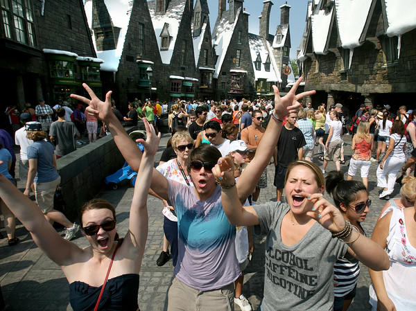 "Three weeks after the attraction's grand opening, Potter fans (from left) Jackie Wooley of <a class=""taxInlineTagLink"" id=""PLGEO100100404010000"" title=""Tampa"" href=""/topic/us/florida/hillsborough-county/tampa-PLGEO100100404010000.topic"">Tampa</a>, Bryan Hall of <a class=""taxInlineTagLink"" id=""PLGEO100101101011251"" title=""Oklahoma City"" href=""/topic/us/oklahoma/oklahoma-county/oklahoma-city-PLGEO100101101011251.topic"">Oklahoma City</a>, Oklahoma, and Lauren Cuervo of Tampa, join others crowding into the <a class=""taxInlineTagLink"" id=""PLGEO000001202118"" title=""Wizarding World of Harry Potter"" href=""/topic/business/tourism-leisure-industry/amusement-theme-parks/wizarding-world-of-harry-potter-PLGEO000001202118.topic"">Wizarding World of Harry Potter</a>, shortly after the <a class=""taxInlineTagLink"" id=""PLENT000186"" title=""Islands of Adventure"" href=""/topic/travel/tourism-leisure/theme-park-vacations/islands-of-adventure-PLENT000186.topic"">Islands of Adventure</a> park opening, Friday morning, July 9, 2010, at Universal Orlando."
