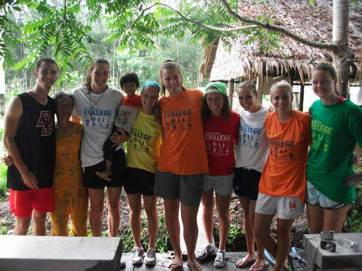 U.Va. basketball palyer Chelsea Shine (third from left carrying child) and other ACC-school students pose for a group shot while in Vietnam for Coach for College, a global initiative to promote higher education founded by former Duke tennis player Parker Goyer.