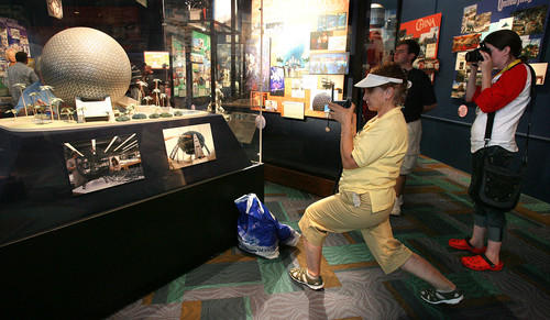 Margarita Sarmiento (center) of Palm Coast and Laura Menssen of St. Paul, Minn. take snapshots of a model rendering of Spaceship Earth during Epcot's 25th anniversary celebration on Monday.