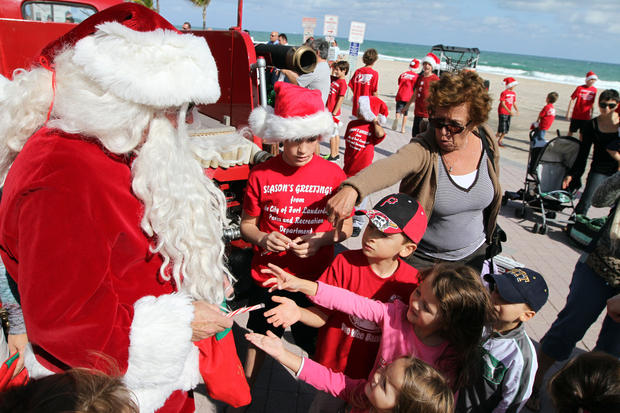 Santa Claus passes out candy canes along Fort Lauderdale Beach.