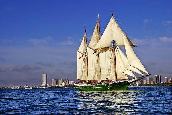 Great Lakes schooner Denis Sullivan, the flagship of Wisconsin, sails on Lake Michigan with the Milwaukee skyline in the background.