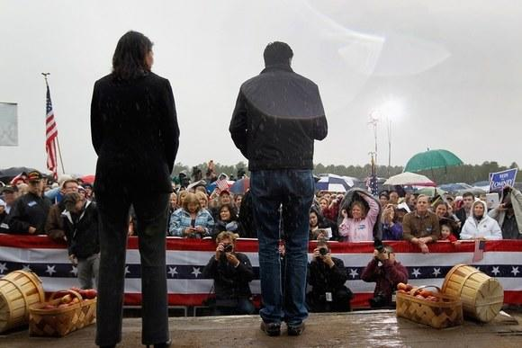 Mitt Romney stands on stage in a rainstorm with South Carolina Gov. Nikki Haley as he speaks during a campaign rally outside a barn at Harmon Tree Farm in Gilbert, S.C.