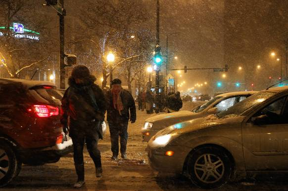 Pedestrians and drivers make the snow commute as snow falls.