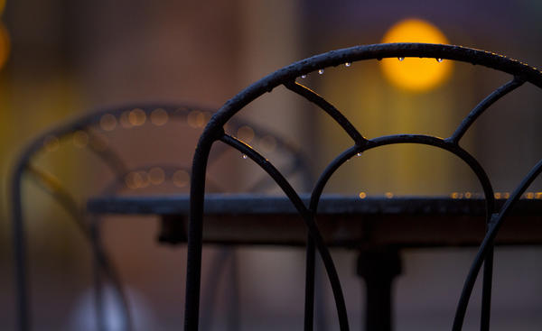 Raindrops gather on unoccupied outdoor furniture at City Center as rain blankets the area with moisture early Monday.