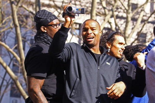 Osi Umenyiora  of the New York Giants films the crowd during the New York Giants ticker tape victory parade down the Canyon of Heros on February 7, 2012 in New York City.