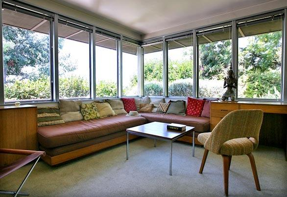 "Along with other modernists, Neutra was driven by a desire to bring in as much air and light into a house as he could and unite indoor and outdoor spaces. Bertram likens this room to a conservatory or screened-in porch.<br> <br> ""In traditional homes, you get a plaster interior with punched-out doors and windows and trim to cover up the seams,"" he says. ""With Neutra, you could have a whole wall of glass panes."" Here, a coffee table in the style of  <a href = ""http://www.knoll.com/designer/designer_detail.jsp?designer_id=83""><u>Florence Knoll</u> </a> and a vintage upholstered chair by Eero Saarinen are part of the couple's decorating sensibility, one that is in keeping with the post-World War II modern aesthetic.<br> <br>  ""Because of the open layout and the built-ins, you really don't need a lot of furniture,"" Bertram says."