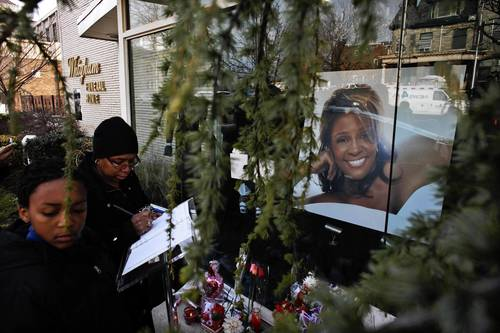 People write messages at the entrance of Whigham Funeral Home, which is handling the funeral service of pop singer Whitney Houston, in Newark, New Jersey.