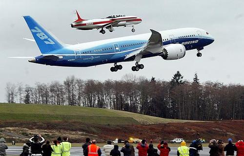 A Boeing 787 Dreamliner passenger jet, escorted by a T33 chase plane, rises from the runway at Paine Field in Everett, Wash., on its first flight.