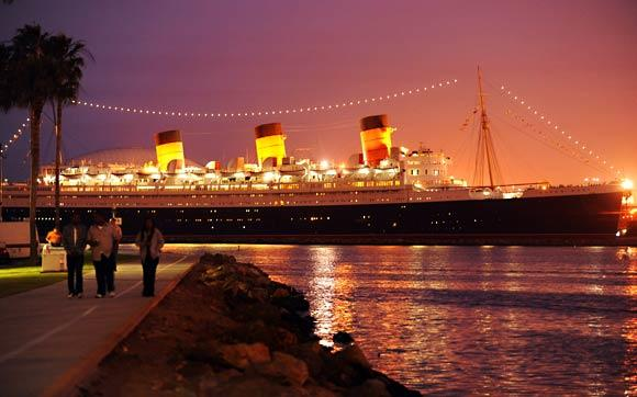 People walk along the shoreline across the bay from the Queen Mary in Long Beach.