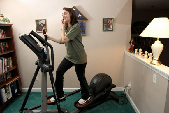 Woman works out on a Nordic Track AudioStrider 990 elliptical at her home.
