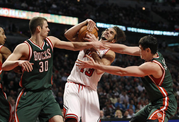 Bulls Joakim Noah battles two Milwaukee Bucks for the ball Wednesday night at the United Center. (Nuccio DiNuzzo/Tribune photo)