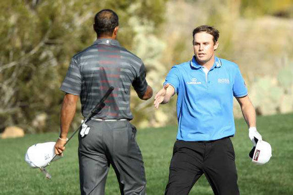 Tiger Woods, left, shakes hands with Nick Watney on the 18th hole after Watney defeated him in the second round of the World Match Play Championship.
