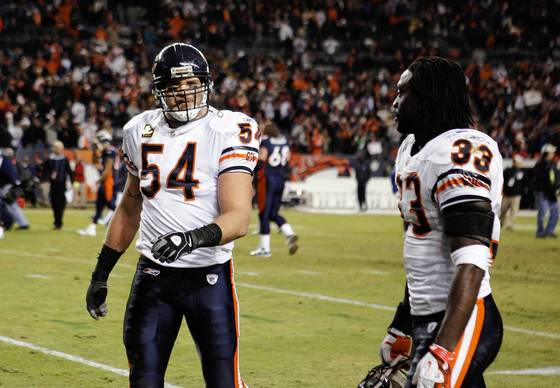 Brian Urlacher and Charles Tillman walk off the field after their team's 13-10 loss in overtime.