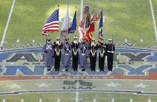 A color guard made up of U.S. Military Academy cadets (in gray) and U.S. Naval Academy midshipmen takes the field prior to the 112th Army-Navy football game.