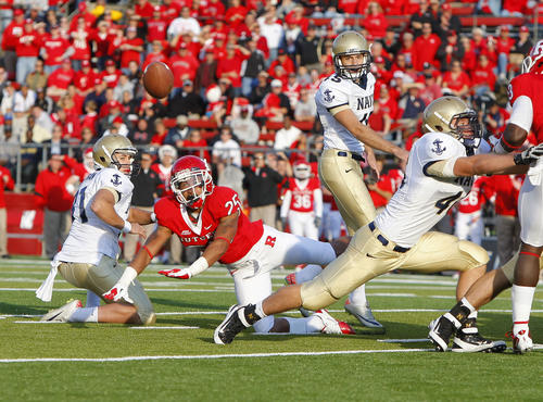 Navy kicker Jon Teague, center, watches as Rutgers' Brandon Jones blocks his 34-yard field-goal attempt with 4:43 left in the game, helping preserve a 21-20 home win for the Scarlet Knights.