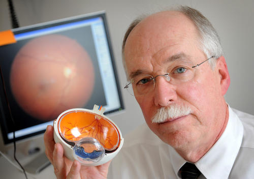James A. Eickhoff, O.D., of Eickhoff and Rowe is pictured in his doctor's office. The screen behind him is part of a Fundus camera which takes pictures of the eyes and reveals any changes including leaking of blood or fluid. Dr. Eickhoff is holding a model of a cross-section of the eye. The orange interior shows the retina with blood vessels that lie directlly on the retina and supply nourishment (also on the screen). Eye doctors are becoming the early detectors of diseases like diabetes and hypertension. By examining the blood vessels of the eye, the doctors can spot these conditions.