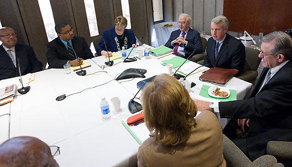 Christopher Kennedy, speaking at right, chairman of the University of Illinois board of trustees, leads a meeting of the trustees today in Chicago. Seated to Kennedy's right is embattled university president Michael Hogan, who has been called on to resign by 130 faculty members.