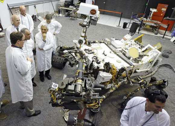 NASA scientists and engineers talk next to a duplicate of the Mars Rover Curiosity at JPL on Wednesday, Feb. 22, 2012.