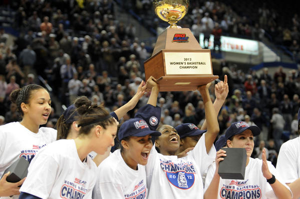 UConn's Tiffany Hayes hoists the Big East trophy as she and teammates pose for photos after they defeated Notre Dame 63-54 in the Big East championship game at the XL Center in Hartford Tuesday night.