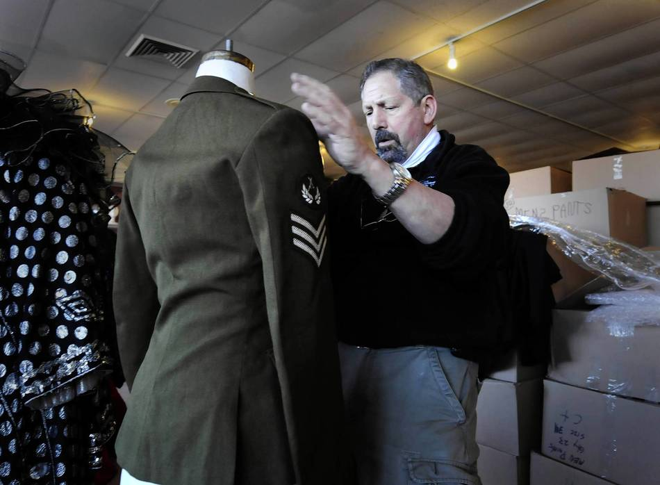 Jeff Russell, owner of the Costume Bazzar in Milford, straightens an autographed jacket worn by Michael Jackson. The jacket is among a few costumes and props worn by celebrities that were auctioned in Milford March 10 and 11. The jacket sold for $9,000.