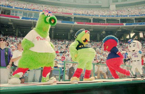 Baseball mascots, from left, The Phillie Phanatic, the Pirate Parrot, Homer the Brave and Mr. Met dance on a dugout at Veterans Stadium in Philadelphia during batting practice for the 1996 All-Star Game.