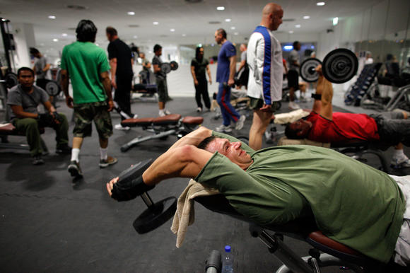 Men work out in a weight room