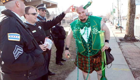 """Evergreen Park's Jamie Keeton, known as """"Can Head"""", passes by some Chicago police officers on his way to the start of the South Side Irish parade today in the Beverly neighborhood."""