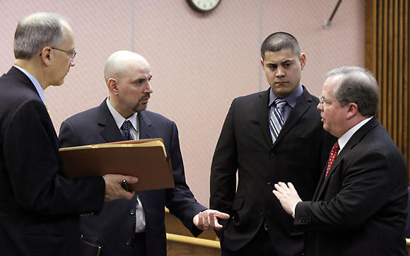 Chuck Hervas (left), attorney representing the Fire and Police Commission, Ray Garza, attorney for Des Plaines police officer Andy Contreras, Contreras and Bob Smith, Council for the City of Des Plaines, (from left) talk before the start of a hearing at the Des Plaines City Hall today.