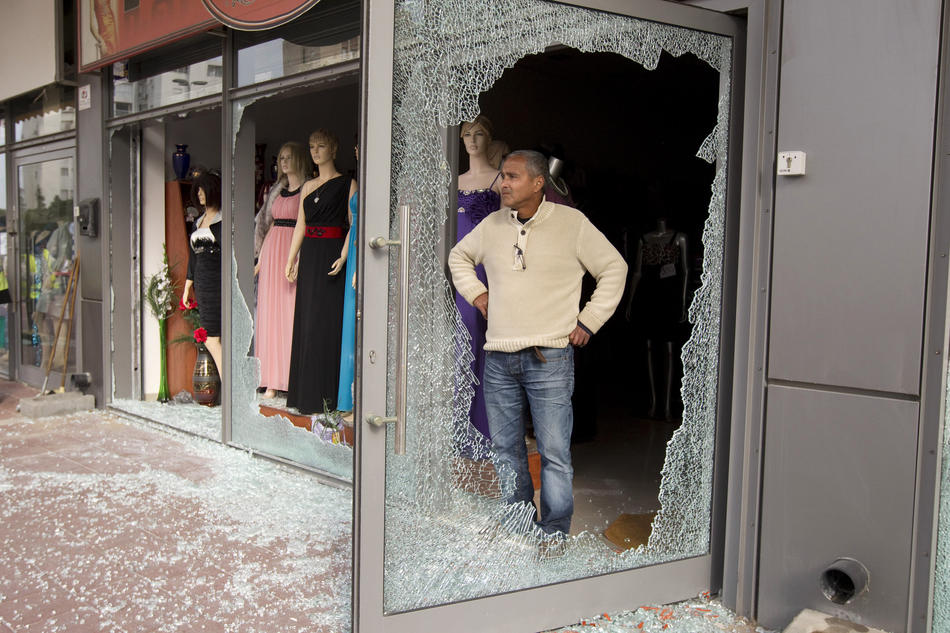 An Israeli man is seen through the broken glass of a shop after a rocket fired by Palestinian militants in the Gaza Strip landed nearby in the southern city of Ashdod