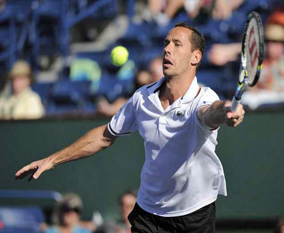 Michael Llodra hits a return against Jo-Wilfried Tsonga on Tuesday. Llodra retired from the match due to a leg injury, perhaps from sticking his foot in his mouth.