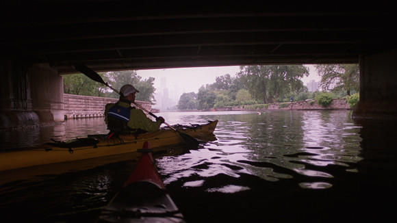 A man kayaking under the Fullerton Avenue bridge over the Lincoln Park Lagoon in May 2004.