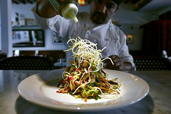 Head chef Ricky Moreno adds a drizzle of olive oil to House Cafe's Chinese chicken salad.