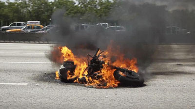 A motorcycle burns in a southbound lane of I-95, in Hollywood, Saturday afternoon, March 17, 2012.  Sgt. Mark Wysocky of Florida Highway Patrol confirmed the accident and stated that there were not serious injuries.