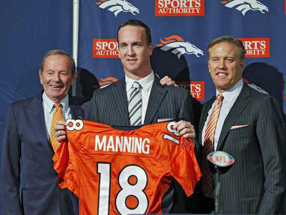 New Denver Broncos quarterback Peyton Manning, center, is flanked by Broncos owner Pat Bowlin, left, and vice president John Elway during a news conference.