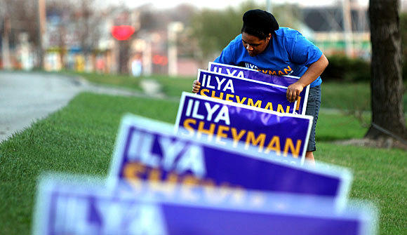 Intern Tayler Morris places signs for Illinois' 10th Congressional democratic primary candidate Ilya Sheyman prior to an election-night gathering for supporters of the candidate from Waukegan.