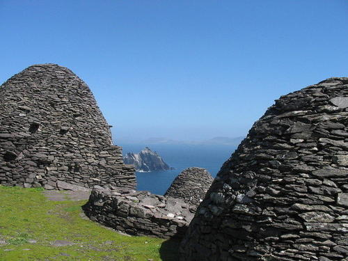 Beehive-shaped huts atop Skellig Michael. In the background is Little Kellig island, a nesting ground for seabirds.