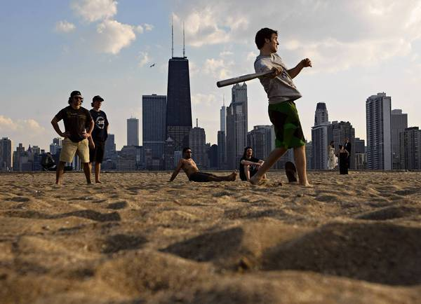 Frederick St. Denis takes a swing at bat on North Avenue Beach during the 85 degree weather.