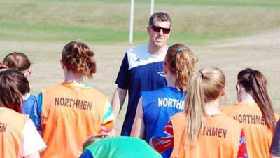 Petoskey High School girls soccer coach Zach Jonker talks to his players during practice Wednesday under sunny skies and tempertures in the upper 70s. Usually forced to practice inside because of the weather in mid-March, the Northmen have now had six outside practices and have already scrimmaged in Midland.