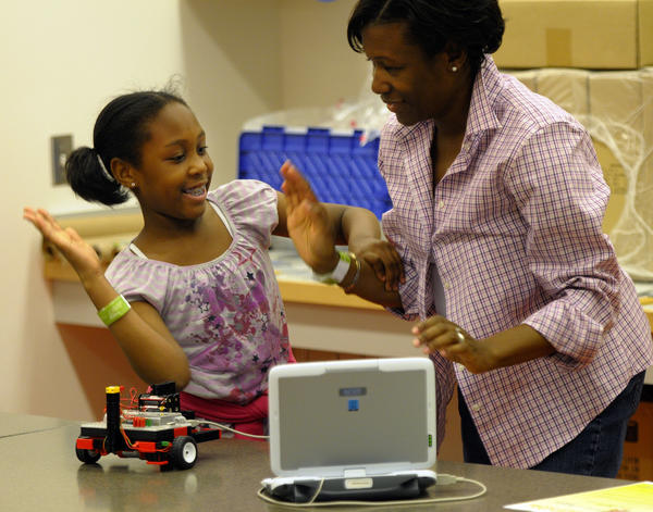 Monica Williams, and her daughter, also Monica Williams, 10, of West Cornwall, celebrate the successful downloading of instructions to their robot so it can be set on the floor to run its course.
