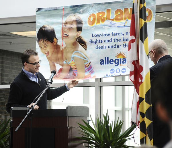 Eric Fletcher, left, manager of airports for Allegiant Air, and Hagerstown Regional Airport Airport Director Phil Ridenour roll down a banner to announce Thursday morning that Allegiant will be providing passenger air service to Orlando, Fla., from Hagerstown beginning in May.