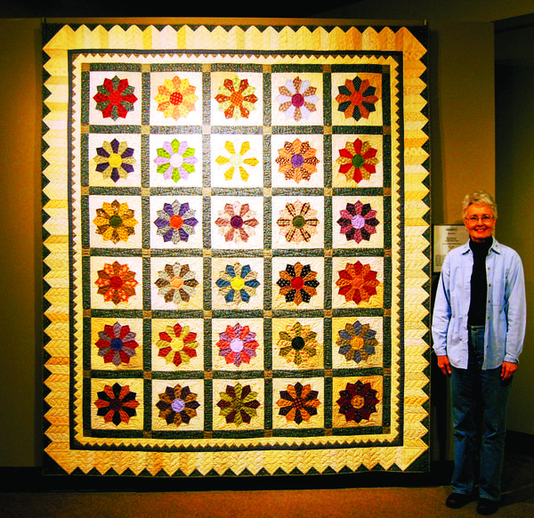 "Patty Prodonovich of Hagerstown stands in front of her quilt, ""Bits and Pieces,"" which is on display at The National Quilt Museum in Paducah, Ky., as part of the museum's ""Quilts of the Appalachian East."""