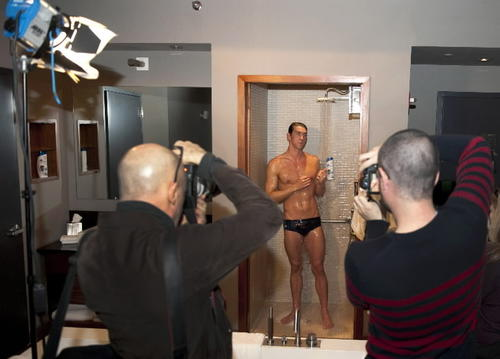 Michael Phelps of the demonstrates how to shower during a photo op in New York.