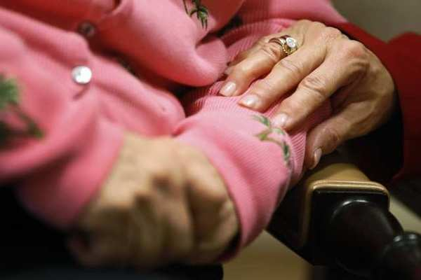 The executive director of The Methodist Home of the District of Columbia Forest Side, an Alzheimer's assisted-living facility, puts her hand on the arm of resident.