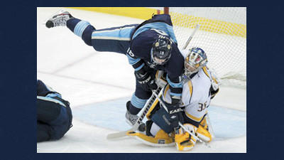 Pittsburgh Penguins' James Neal (18) collides with Nashville Predators goalie Pekka Rinne (35) in the first period of an NHL hockey game Thursday in Pittsburgh.
