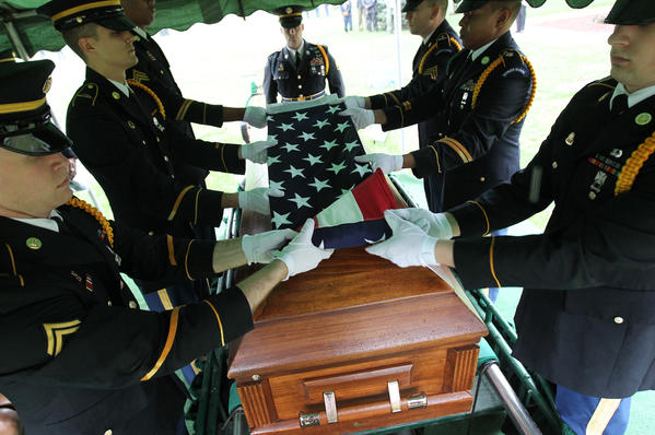 The Military Honor Guard folds up the American flag for presentation to Charlene Byrd, during funeral services at Evergreen Park Cemetery for Korean war POW Army Cpl. Chester Roper. Roper was buried and unknown for 60 years. His remains were identified late last year.