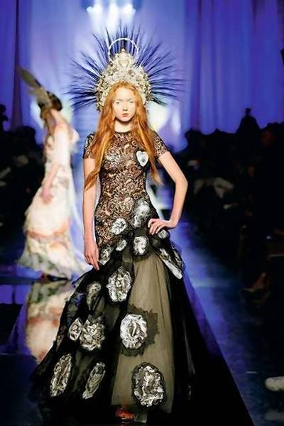 "Jean Paul Gaultier's ""Dolorès"" gown from the spring-summer 2007 collection features a black guipure top over an ivory silk tulle underskirt with religious-motif jacquard medallion appliqués."