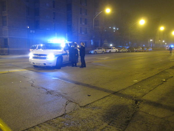 Police work near the scene of a hit-and-run car crash Saturday morning. A vehicle hit a man and fled the scene but was later caught, police said.