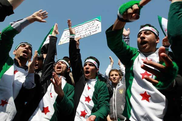 Syrian protesters living in Jordan shout slogans during a demonstration in Amman.
